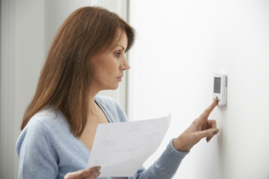 A woman turning down her thermostat